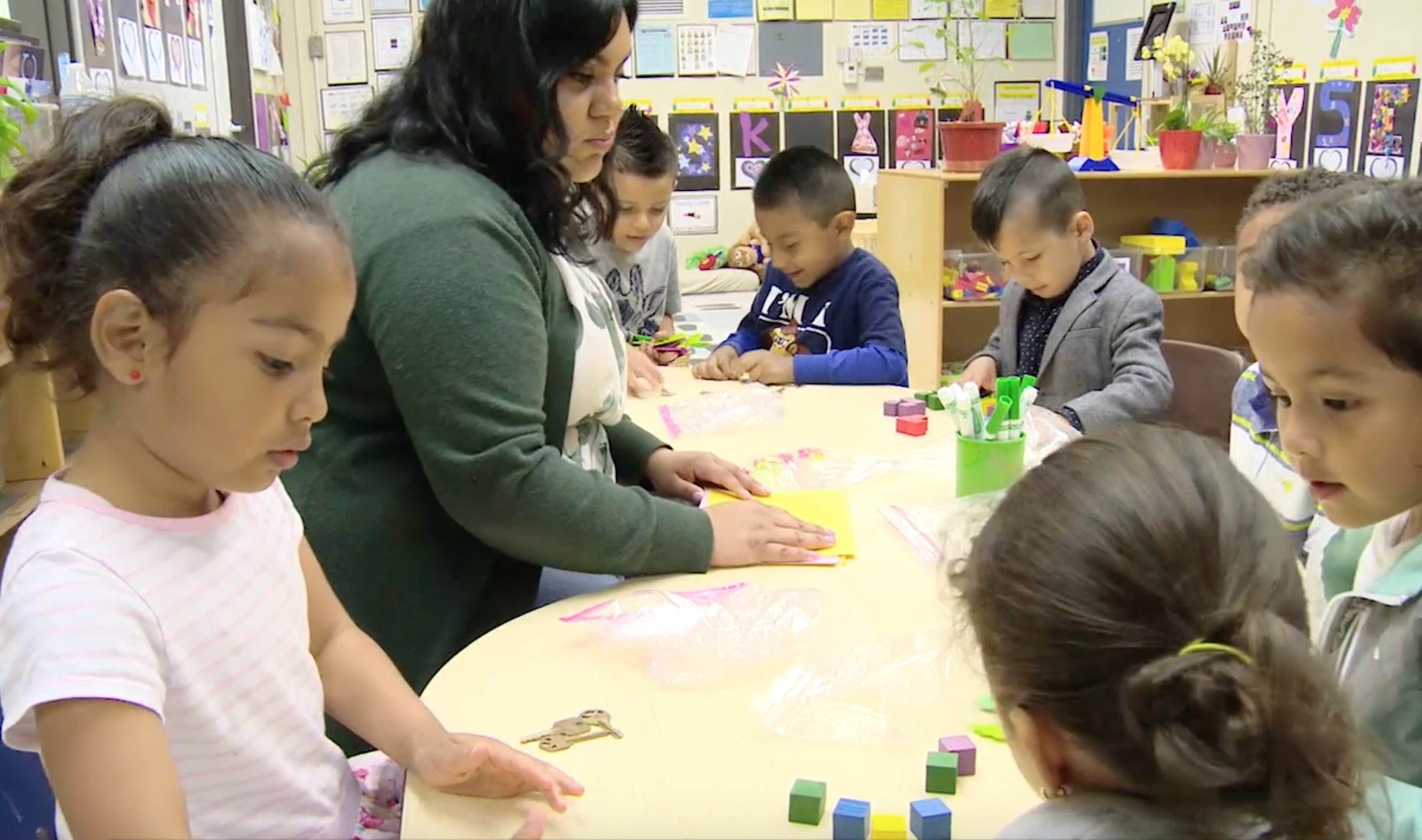 preschool teacher and small group of children counting collections