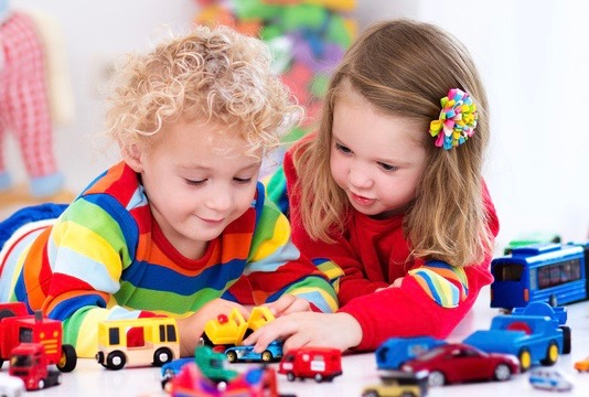 two preschool children playing trucks